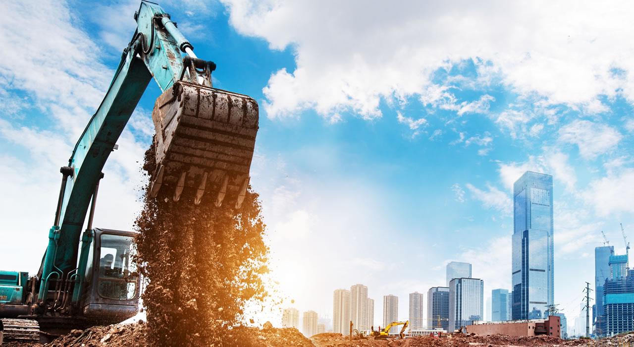 modry bager vysypa hlinu, v pozadi mrakodrapy